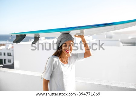Portrait of a young smiling woman in white t-shirt and hat carrying surfboard on the white city background. Active water sport vacations