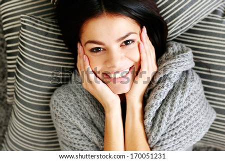 Portrait of a young smiling woman lying on the floor with pillows. View from above - stock photo