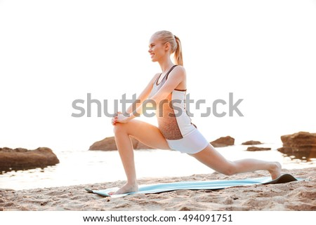 Portrait of a young smiling woman stretching legs outdoors on beach