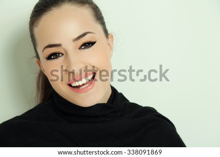 portrait of a young smiling woman with elegant makeup, studio