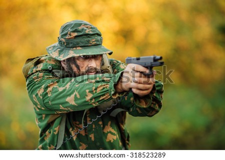 portrait of a young soldier aiming and shooting with a pistol