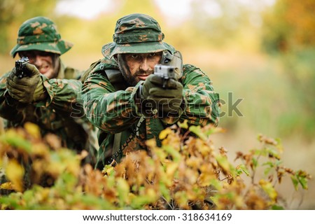 portrait of a young soldier aiming and shooting with a pistol - stock photo