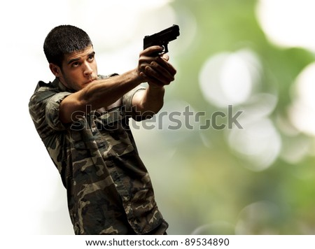 portrait of a young soldier aiming with pistol against a nature background
