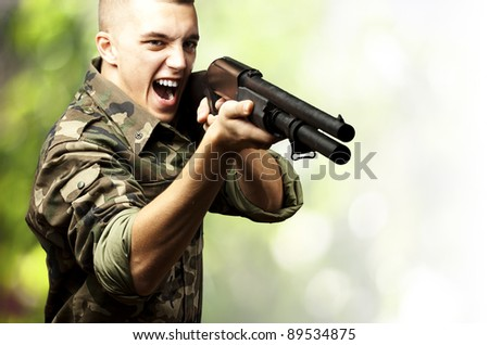 portrait of a young soldier aiming with shotgun against a nature background - stock photo