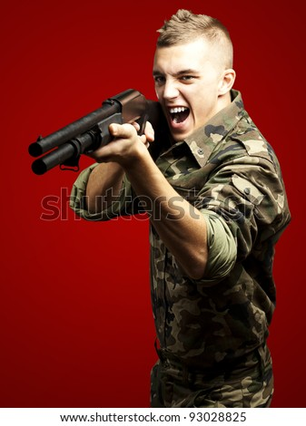 portrait of a young soldier aiming with shotgun against a red background - stock photo