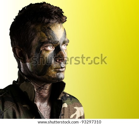 portrait of a  young soldier face with jungle camouflage against a yellow background