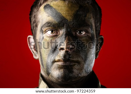portrait of a young soldier face with jungle camouflage paint against a red background - stock photo