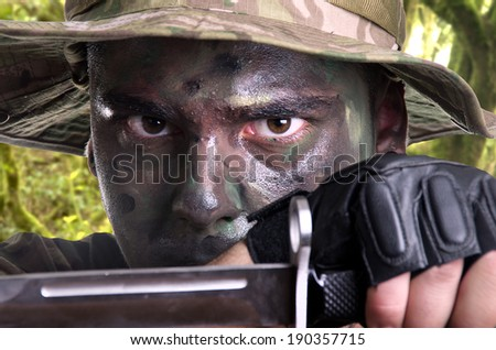 portrait of a young soldier painted with jungle camouflage very serious
