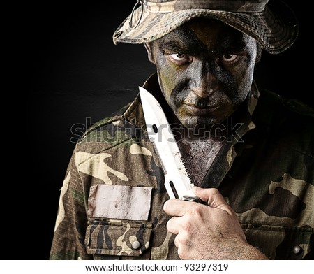 portrait of a young soldier threatening to suicide over a black background - stock photo