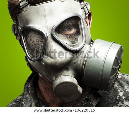 portrait of a young soldier wearing a gas mask against a green background