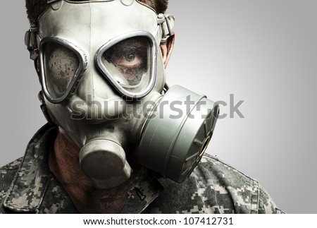 portrait of a young soldier wearing a gas mask against a grey background - stock photo