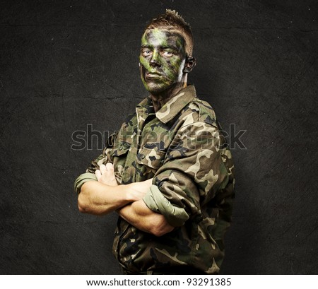 portrait of a young soldier with jungle camouflage paint against a grunge background - stock photo