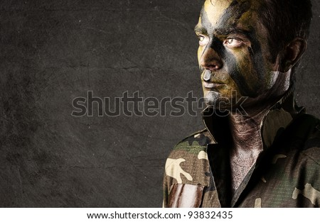 portrait of a young soldiers face painted with jungle camouflage against a grunge wall - stock photo