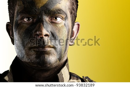 portrait of a young soldiers face with jungle camouflage paint against a yellow background - stock photo