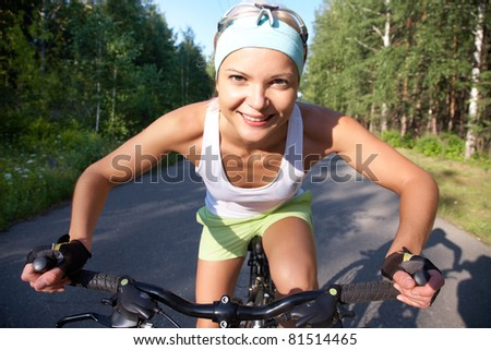 Portrait of a young sports cute girl on a bicycle in the park