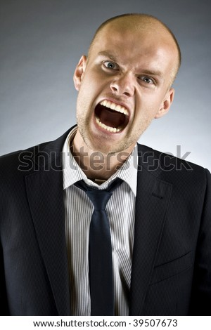 portrait of a young strong and screaming man isolated on dark  background