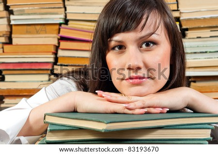 Portrait of a young student against piled up books - stock photo