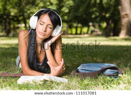 Portrait of a young student girl relaxing, studying outdoors in the park. - stock photo