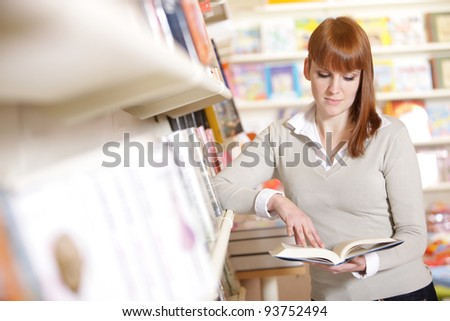 portrait of a  young  student in a library - stock photo