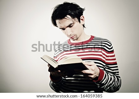 Portrait of a young student reading a textbook - stock photo
