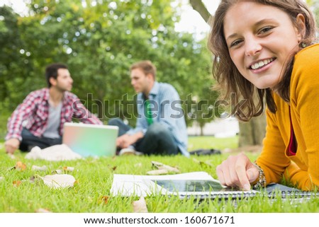 Portrait of a young student using tablet PC while two males using laptop in background at the park - stock photo