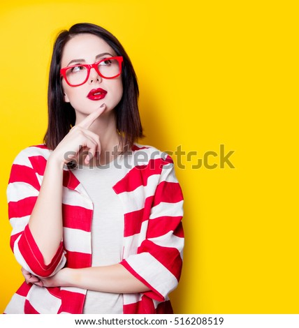 Portrait of a young style woman in glasses on yellow background