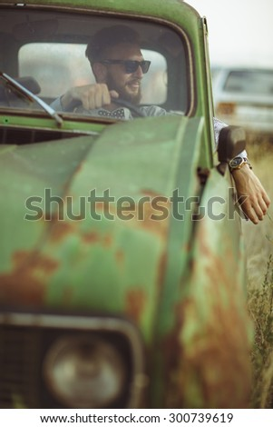 Portrait of a young stylish handsome man, wearing shirt and sunglasses, driving old car - stock photo