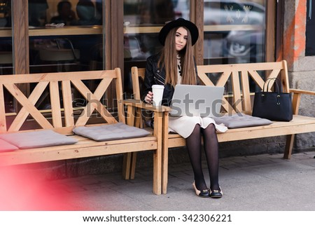 Portrait of a young stylish woman working on portable laptop computer while sitting outdoors in the coffee shop, pretty smart female with trendy look using net-book for remote job during her weekend  - stock photo