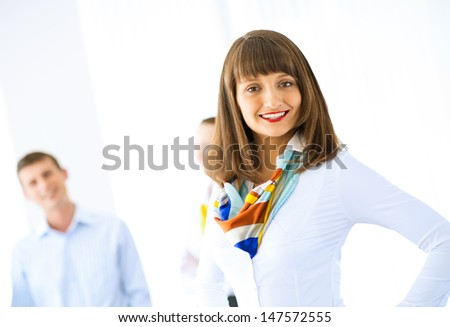 Portrait of a young successful business woman standing against colleagues