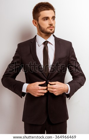 Portrait of a young successful businessman in a business suit on a gray background - stock photo
