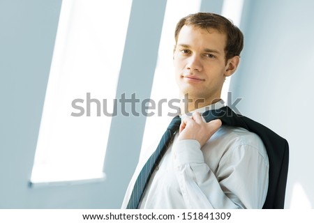 Portrait of a young successful businessman in bright office