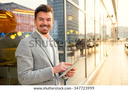 Portrait of a young successful businessman on background of office center - stock photo