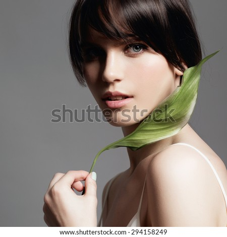Portrait of a young sweet girl in the studio on a gray background with a green flower in hand, the concept of beauty and health - stock photo