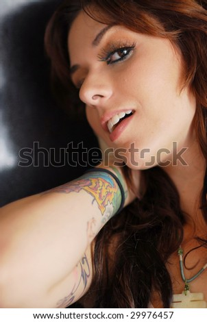 Portrait of a young tattooed brunette woman with shadow - stock photo