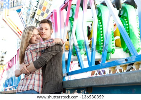 Portrait of a young teenage couple hugging while enjoying together being in a funfair ground with rides in the background, smiling.