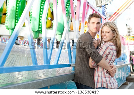 Portrait of a young teenage couple hugging while enjoying together being in a funfair ground with rides in the background, smiling. - stock photo