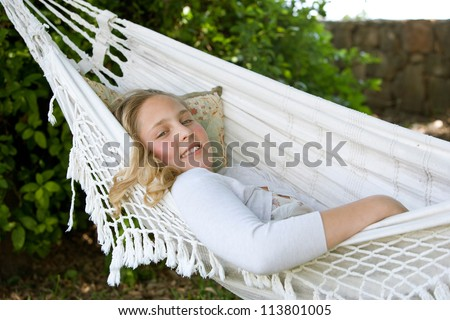 Portrait of a young teenage girl laying down and relaxing on a hammock in a garden, smiling. - stock photo