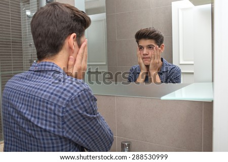 Portrait of a young teenager man looking at himself in a home bathroom mirror, getting ready in the morning and looking worried, home interior. Health and well being, male care and grooming, indoors. - stock photo