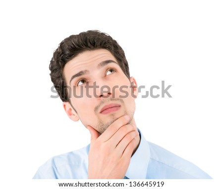 Portrait of a young thoughtful businessman looking up at copyspace. Isolated on white background. - stock photo