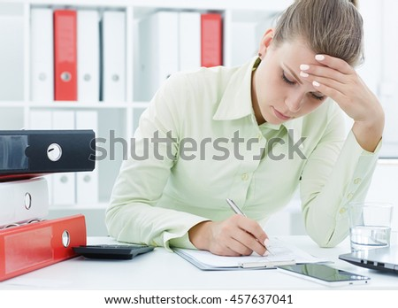 Portrait of a young tired businesswoman working with documents on the desk.