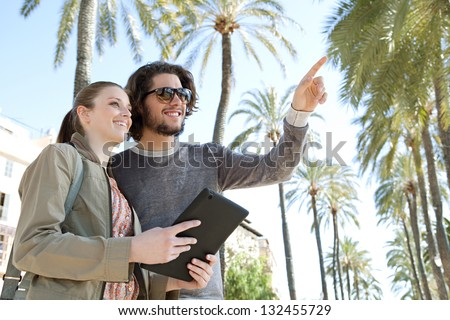 Portrait of a young tourist couple on vacation in a destination city palm trees boulevard, holding a technology tablet during a sunny day and pointing ahead. - stock photo