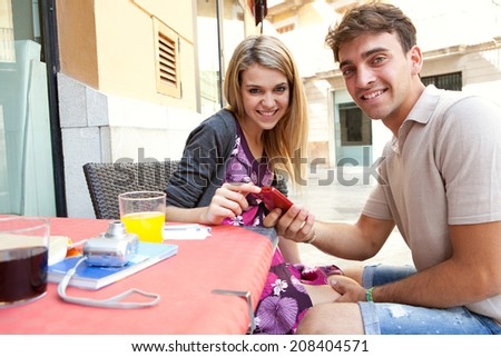 Portrait of a young tourist couple sitting together at a cafe terrace with refreshments and shopping bags, visiting a destination city and using smartphone outdoors. Technology travel lifestyle. - stock photo