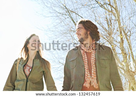 Portrait of a young tourist couple walking together with winter trees and a blue sky in the background, smiling while on vacation. - stock photo
