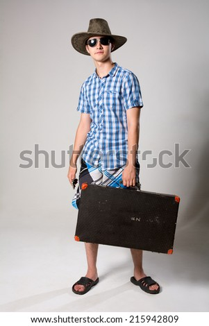 Portrait of a young tourist in a full-length looking away. A man wearing sunglasses and a hat holding a suitcase - stock photo