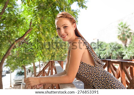 Portrait of a young tourist woman leaning on a wooden banister balcony in a leafy street on holiday, smiling, exterior. Travel and lifestyle summer vacation, outdoors park. Smart woman, lifestyle. - stock photo