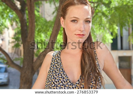 Portrait of a young tourist woman smiling in a leafy street on holiday, exterior. Travel and lifestyle summer vacation, outdoors park. Smart woman, lifestyle. Fresh natural beauty portrait. - stock photo