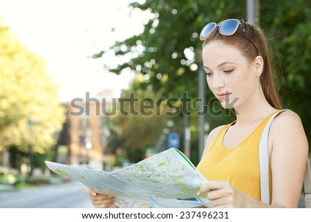 Portrait of a young tourist woman visiting a classic destination city with old buildings and trees during a sunny day, holding and reading a street map finding directions. Travel lifestyle, outdoors. - stock photo