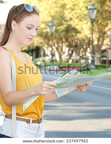 Portrait of a young tourist woman visiting a destination city with stone buildings and green trees during a sunny day, holding and reading a street map finding directions. Travel lifestyle, outdoors. - stock photo