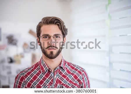 Portrait of a young trendy man wearing glasses and beard - stock photo