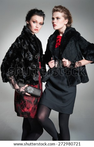 portrait of a young two woman with fur coat ,a purse posing - stock photo